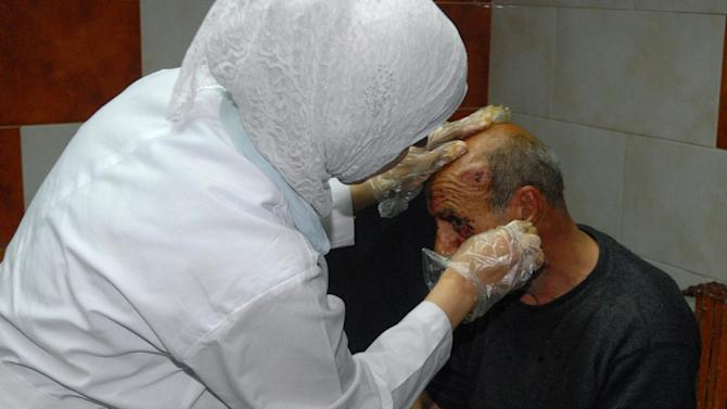 In this photo released by the Syrian official news agency SANA, a Syrian doctor, left, treats an injured man who was wounded at the Eman Mosque where a suicide bomber blew himself up, killing Sheikh Mohammad Said Ramadan al-Buti, an 84-year-old cleric known to all Syrians as a religious scholar, at the Mazraa district, in Damascus, Syria, Thursday, March 21, 2013. A suicide bomber blew himself up during evening prayers inside a mosque in Damascus Thursday, killing a top Sunni Muslim preacher and longtime supporter of President Bashar Assad and least 13 other people, state TV reported. Al-Buti's death is a big blow to Syria's embattled leader, who is fighting mainly Sunni rebels seeking his ouster. (AP Photo/SANA)