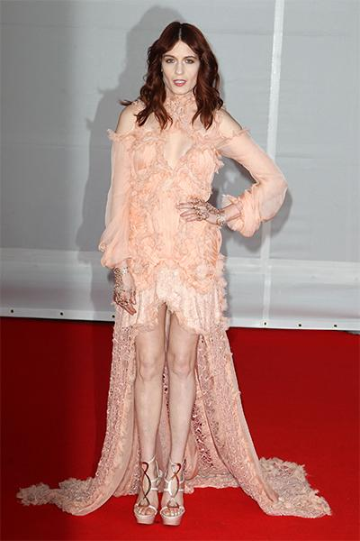 Florence hit the red carpet at the 2012 Brit Awards in an approximately $19,000 Alexander McQueen blush-colored, ruffled and bead-embellished lace and chiffon gown with cut out shoulders and cleavage,