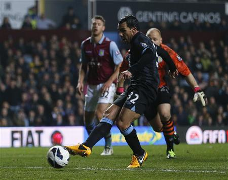 Manchester City's Carlos Tevez goes past Aston Villa goalkeeper Brad Guzan to score his goal during their English Premier League soccer match at Villa Park in Birmingham