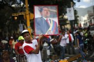A supporter of Venezuela&#39;s President Hugo Chavez holds up a portrait of him while attending a rally in Caracas February 27, 2013. REUTERS/Jorge Silva