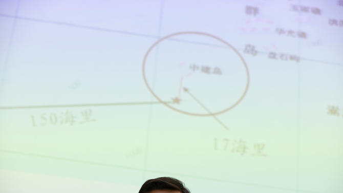 In this May 8, 2014 photo, Yi Xianliang, deputy director-general of Chinese Ministry of Foreign Affairs' Department of Boundary and Ocean Affairs, attends a press conference in front of a map showing a disputed zone in South China Sea, in Beijing, China. China's planting of an oil platform in contested waters off Vietnam drew strident complaints from Hanoi, a messy standoff between ships and violent protests among Vietnamese, but nothing to dislodge the rig and no broader pushback in the region. (AP Photo/Alexander F. Yuan)