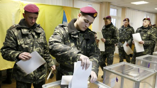 A Ukrainian serviceman casts a ballot during a parliamentary election at a polling station in Kiev