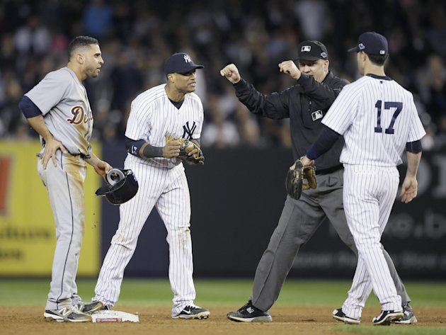 Umpire Jeff Nelson is approached by New York Yankees' Robinson Cano, left, and Jayson Nix after calling Detroit Tigers' Omar Infante safe at second base in the eighth inning of Game 2 of the American