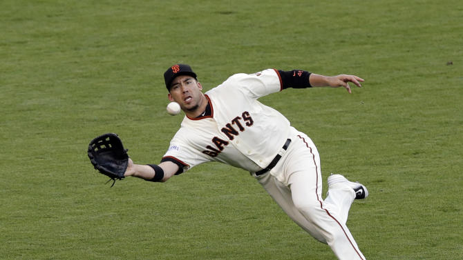 San Francisco Giants first baseman Travis Ishikawa catches a fly ball by Kansas City Royals Salvador Perez during the second inning of Game 3 of baseball's World Series Friday, Oct. 24, 2014, in San Francisco. (AP Photo/Jeff Chiu)