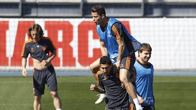 Real's Cristiano Ronaldo, top, jumps on top of Angel Di Maria from Argentina during a training session Champions League round of 16, second leg, soccer match between FC Schalke 04 and Real Madrid in Madrid, Spain, Monday March 17, 2014. (AP Photo)