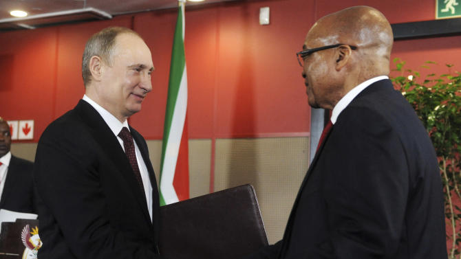 Russian President  Vladimir Putin and  South African President Jacob Zuma exchange documents after signing the Declaration of State Partnership between South Africa and Russia at the BRICS 2013 Summit in Durban, South Africa,  Tuesday, March 26, 2013. Heads of State of BRICS nations (Brazil, Russia, India and China) meet in the South Africa city of Durban for the two day summit. (AP Photo/S Mngoma)