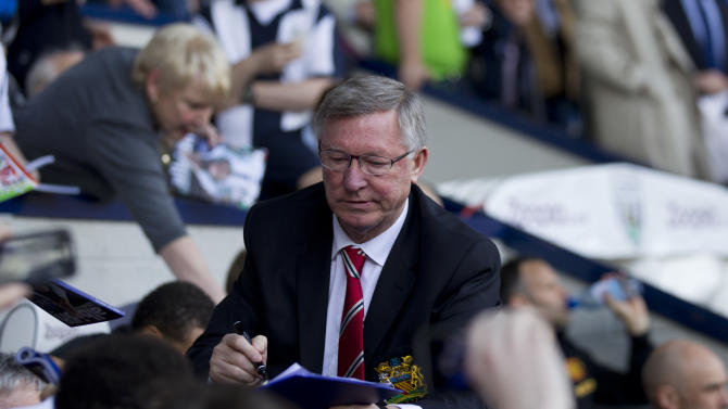 Manchester United manager Sir Alex Ferguson signs autographs before his last game in charge of his team, their English Premier League soccer match against West Bromwich Albion at The Hawthorns Stadium, West Bromwich, England, Sunday May 19, 2013. (AP Photo/Jon Super)