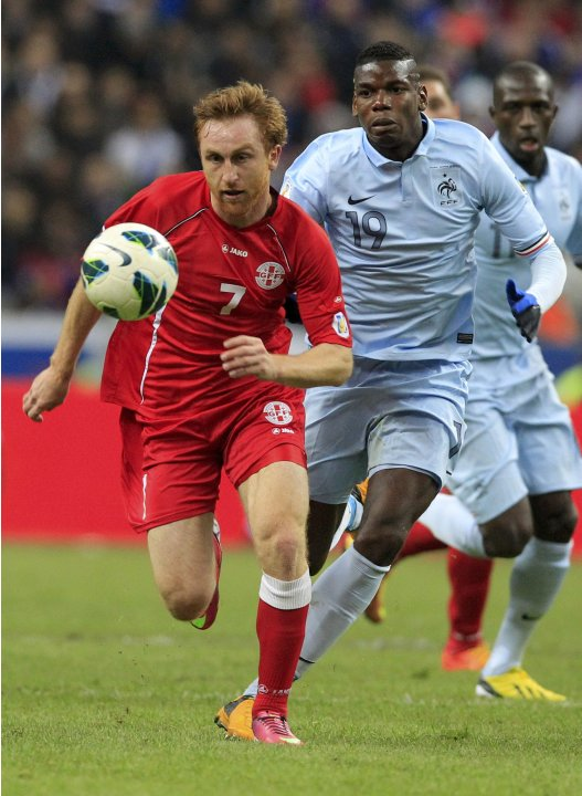 Georgia's Kobakhidze challenges France's Pogba during their 2014 World Cup qualifying match at the Stade de France stadium in Saint-Denis