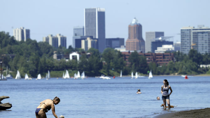 People, pets and sailors use the Willamette River to cool off in Portland, Ore., Monday, July 6, 2015. People were out in droves in the river trying to keep cool from an extended heat wave with higher than normal temperatures for this time of year. (AP Photo/Don Ryan)