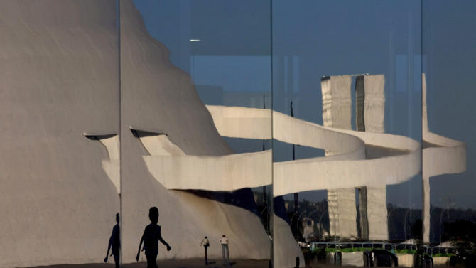 FILE - In this April 7, 2010 file photo, the National Museum and National Congress are reflected on the glass wall of the National Library, all designed by architect Oscar Niemeyer, in Brasilia, Brazil. According to a hospital spokeswoman on Wednesday, Dec. 5, 2012, famed Brazilian architect Oscar Niemeyer has died at age 104.  (AP Photo/Eraldo Peres, File)