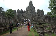 Visitors walk the ruins of Bayon in the center of Angkor Thom May 27, 2002 in Angkor, Cambodia. Built as a Buddhist temple around 1300 A.D., just after the construction of Angkor Wat nearby, Angkor Thom served as the center for the Khmer Empire, despite being physically threatened under the Khmer Rouge regime of the 1970-80s. As restoration efforts continue to preserve the many temples in Angkor, tourism also has boomed in recent years. (Photo by David Greedy/Getty Images)