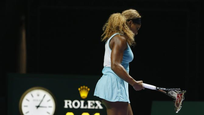 Serena Williams of the U.S. walks off the court with her second broken racquet during her WTA Finals singles semi-finals tennis match against Caroline Wozniacki of Denmark, at the Singapore Indoor Stadium