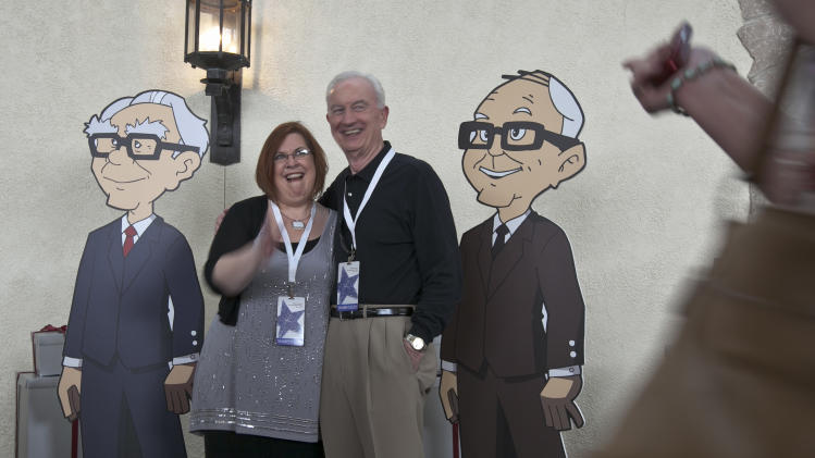 Shareholders pose with cardboard cartoons of Berkshire Hathaway chairman and CEO Warren Buffett, left, and his vice chairman Charlie Munger outside the Berkshire-owned Borsheims jewelry store in Omaha, Neb., Friday, May 4, 2012. Berkshire Hathaway is expected to have 30,000 shareholders come to Omaha for it's annual shareholders meeting this weekend. (AP Photo/Nati Harnik)