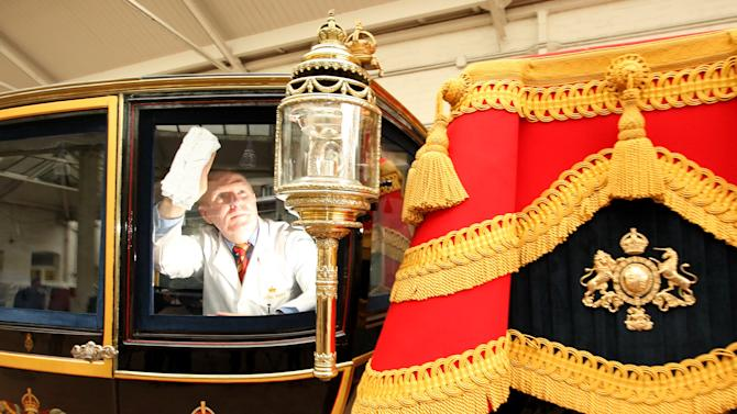 Carriage restorer, Dave Evans, cleans the windows of the Glass Coach at the Royal Mews in central London, Monday March 21, 2011. The coach, which was built in 1881, and is traditionally used by Royal brides to travel on their wedding day, will be used to carry Prince William and Kate Middleton in the event of bad weather on their wedding day on Friday, April 29, 2011. Should the weather be good on the day then the 1902 State Landau carriage will be used instead. (AP Photo/Dominic Lipinski, Pool)