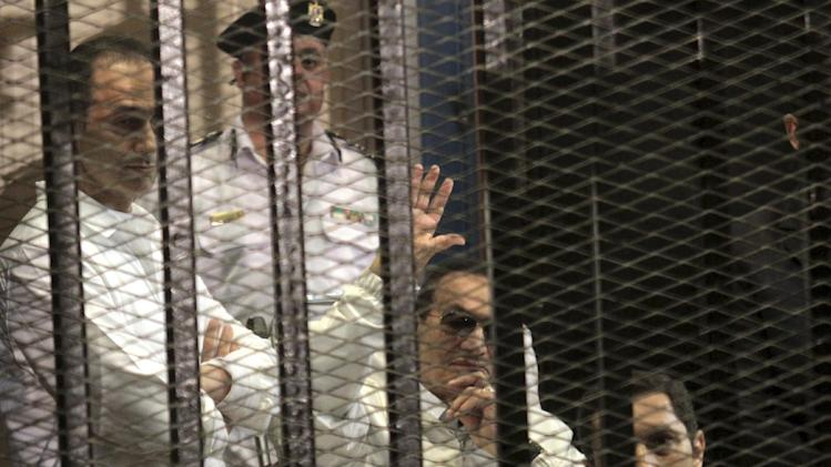 Former Egyptian President Hosni Mubarak, second right, waves at his supporters, who with his sons Alaa, right, and Gamal. left attend a hearing in their retrial on appeal in Cairo, Egypt, Saturday, April 13, 2013. Egypt's highest court in January ordered a retrial for Mubarak, for failing to stop the killing of 900 protestors in the 2011 unrest that ousted him, after accepting an appeal against his life sentence, citing procedural failings. The sons face corruption charges. (AP Photo/ Tarek el Gabbas)