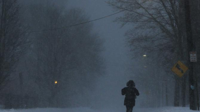 A pedestrian walks along a snow covered road during a large winter blizzard in Cambridge