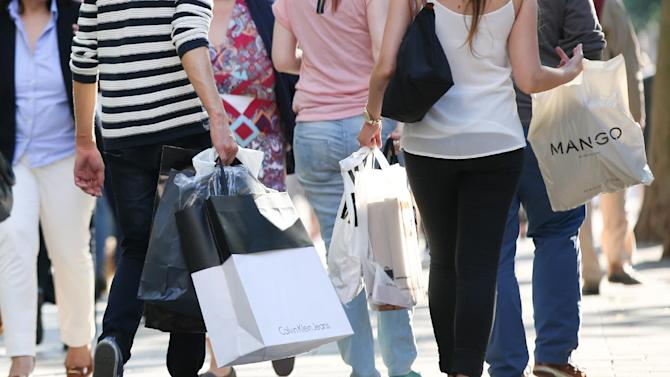 """FILE - In this June 6, 2014 file picture persons walk with shopping bags in Hamburg, Germany. A closely-watched survey shows economic expectations among German consumers have """"completely collapsed"""" over concerns about the conflicts in Iraq, Israel and Ukraine. The GfK institute said Wednesday Aug. 27, 2014 its latest index of economic expectations slid 35.5 points in August to 10.4 — the largest one-month decline since the survey began in 1980. Its headline forward-looking consumer climate indicator also fell to 8.6 for September from 8.9 in August. (AP Photo/dpa, Bodo Marks,file)"""