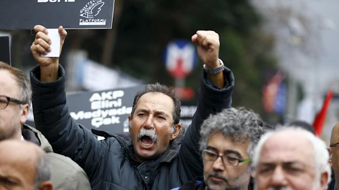 Demonstrators shout slogans during a protest outside the headquarters of Cumhuriyet newspaper