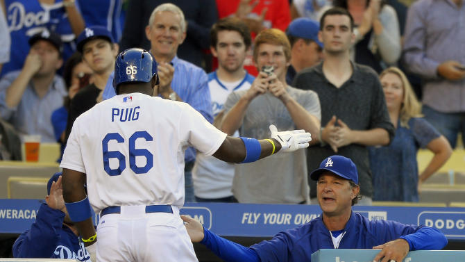Los Angeles Dodgers' Yasiel Puig, left, is congratulated by manager Don Mattingly after hitting a solo home run during the first inning of their baseball game, Monday, June 24, 2013, in Los Angeles. (AP Photo/Mark J. Terrill)