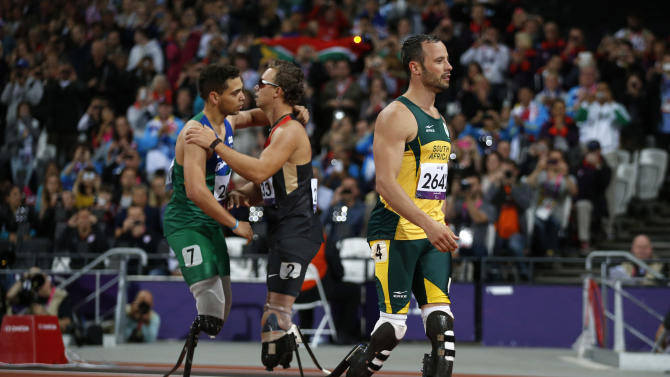 Gold medal winner Brazil's Alan Fonteles Cardoso Oliveira, left, embraces Germany's David Behre, center, as silver medalist south Africa's Oscar Pistorius walks away after they ran the men's 200m T44 category final during the athletics competition at the 2012 Paralympics, Sunday, Sept. 2, 2012, in London.  (AP Photo/Matt Dunham)