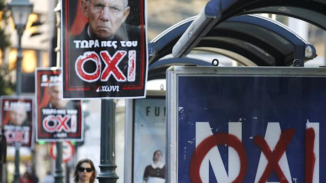 A referendum campaign poster that reads 'Yes (Nai)' is seen on a bus stop with a graffiti that reads 'No (Oxi)' on it in Athens
