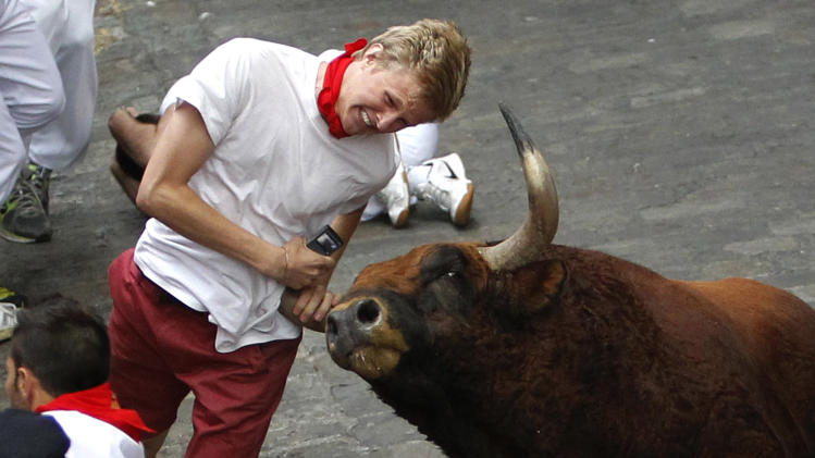 "A runner is gored by an ""El Pilar"" fighting bull during the running of the bulls at the San Fermin festival, in Pamplona, Spain, Friday, July 12, 2013. An American and two Spaniards were gored Friday during a danger-filled sixth bull run of Spain's San Fermin festival, with one loose bull causing panic in the packed streets of Pamplona city. (AP Photo) SPAIN OUT"