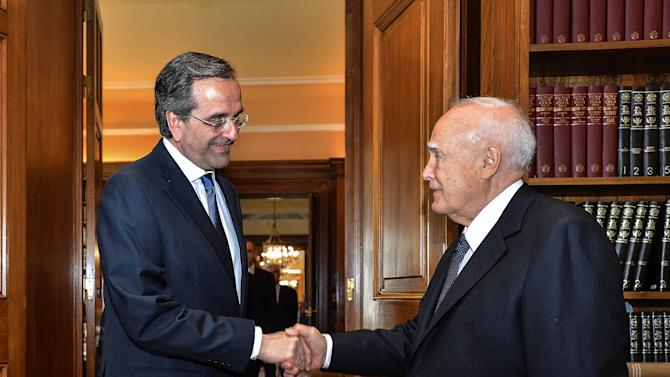 The head of Greece's conservative  New Democracy party, Antonis Samaras, left, shakes hands with President Carolos Papoulias  in Athens on Wednesday June 20, 2012.  Samaras was sworn in as prime minister Wednesday at the helm of a three-party coalition that will uphold the country's international bailout commitments. The move ends a protracted political crisis that had cast grave doubt over the country's future in Europe's joint currency and threatened to plunge Europe deeper into a financial crisis with global repercussions.  (AP Photo/Andreas Solaro,pool)