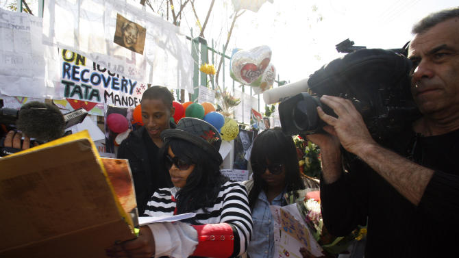 Unidentified members of the family are swamped by the media after collecting flowers from wellwishers outside the Mediclinic Heart Hospital where former South African President Nelson Mandela is being treated in Pretoria, South Africa, Thursday, June 27, 2013. President Jacob Zuma canceled a trip to Mozambique on Thursday in an indication of heightened concern about Mandela, whose health deteriorated last weekend. (AP Photo/Themba Hadebe)
