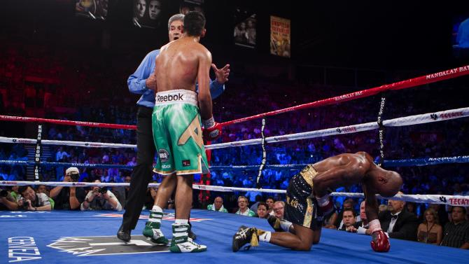 Amir Khan, of Bolton, England, knocks down Zab Judah during the fifth round of their IBF & WBA junior welterweight title boxing match, Saturday, July 23, 2011, at Mandalay Bay Resort & Casino in Las Vegas. Khan won the fight moments later by TKO. (AP Photo/Eric Jamison)