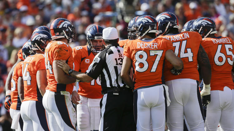 referee Pete Morelli (135) confers with Denver Broncos quarterback Peyton Manning (18) and the Denver Broncos during the second quarter of an NFL football game, Sunday, Sept. 30, 2012, in Denver. (AP Photo/Joe Mahoney)