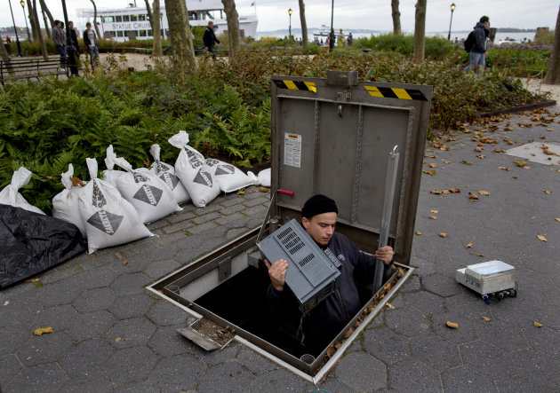 <p>               A technician with the Battery Conservancy removes below-ground fountain operation equipment near the water's edge at Battery Park in New York, Sunday, Oct. 28, 2012. Areas in the Northeast are preparing for the arrival of Hurricane Sandy and a possible flooding storm surge. (AP Photo/Craig Ruttle)