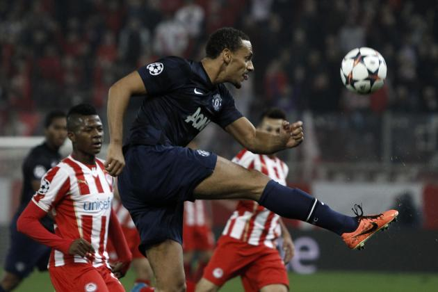 Manchester United's Ferdinand shoots the ball in front of Olympiakos' Olaitan during their Champions League round of 16 first leg soccer match at Karaiskaki stadium in Piraeus, near Athens