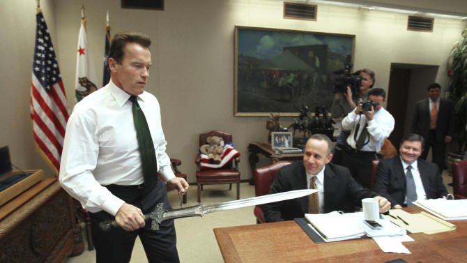 "FILE - In this Jan. 13, 2009 file photo, Gov. Arnold Schwarzenegger brings the sword he used in the movie ""Conan The Barbarian,"" to the conference table before the start of budget negotiations with legislative leaders at the Capitol in Sacramento, Calif. Schwarzenegger, who came to office during California's historic 2003 recall election, will  soon be releasing his autobiography, ""Total Recall: My Unbelievably True Life Story.""(AP Photo/Rich Pedroncelli, file)"