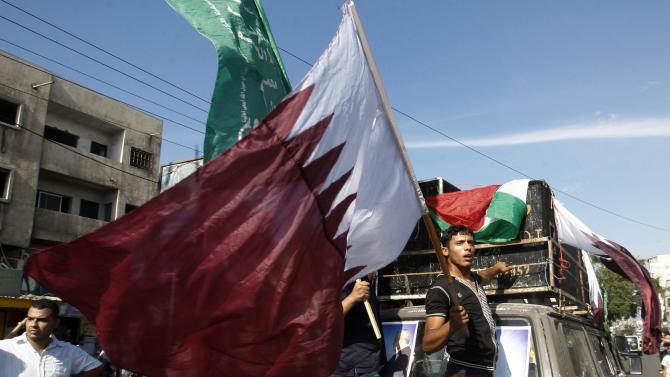 A Palestinian waves a Qatari flag as he and others wait on Gaza's main road for the convoy of the Qatari Emir Sheikh Hamad bin Khalifa Al-Thani to arrive in Gaza City, Tuesday, Oct. 23, 2012. The emir of Qatar received a hero's welcome in Gaza on Tuesday, becoming the first head of state to visit the Palestinian territory since the Islamist militant Hamas seized control there in 2007. (AP Photo/Hatem Moussa)