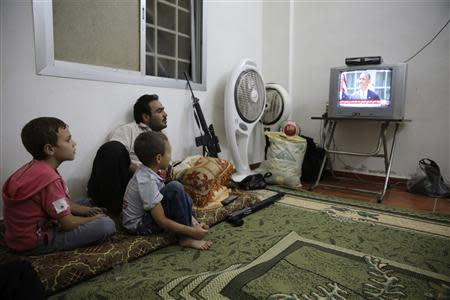 A Free Syrian Army fighter watches U.S. President Barack Obama's speech with his family in Damascus