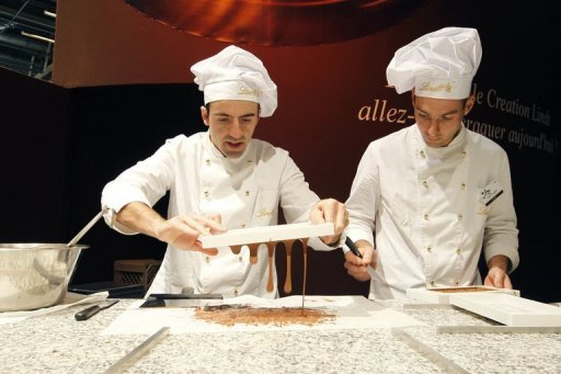 "<p>Chocolate makers from Swiss company Lindt & Sprüngli work on chocolate during the inaugural evening of the 16th ""Salon du Chocolat"" (chocolate fair) in Paris in 2010. Lindt and Spruengli said Tuesday its 2012 first-half net profit rose 14 percent on the same period in 2011 to 36.6 million francs (30.4 million euros, $37.7 million) despite difficult conditions in Europe and the United States.</p>"