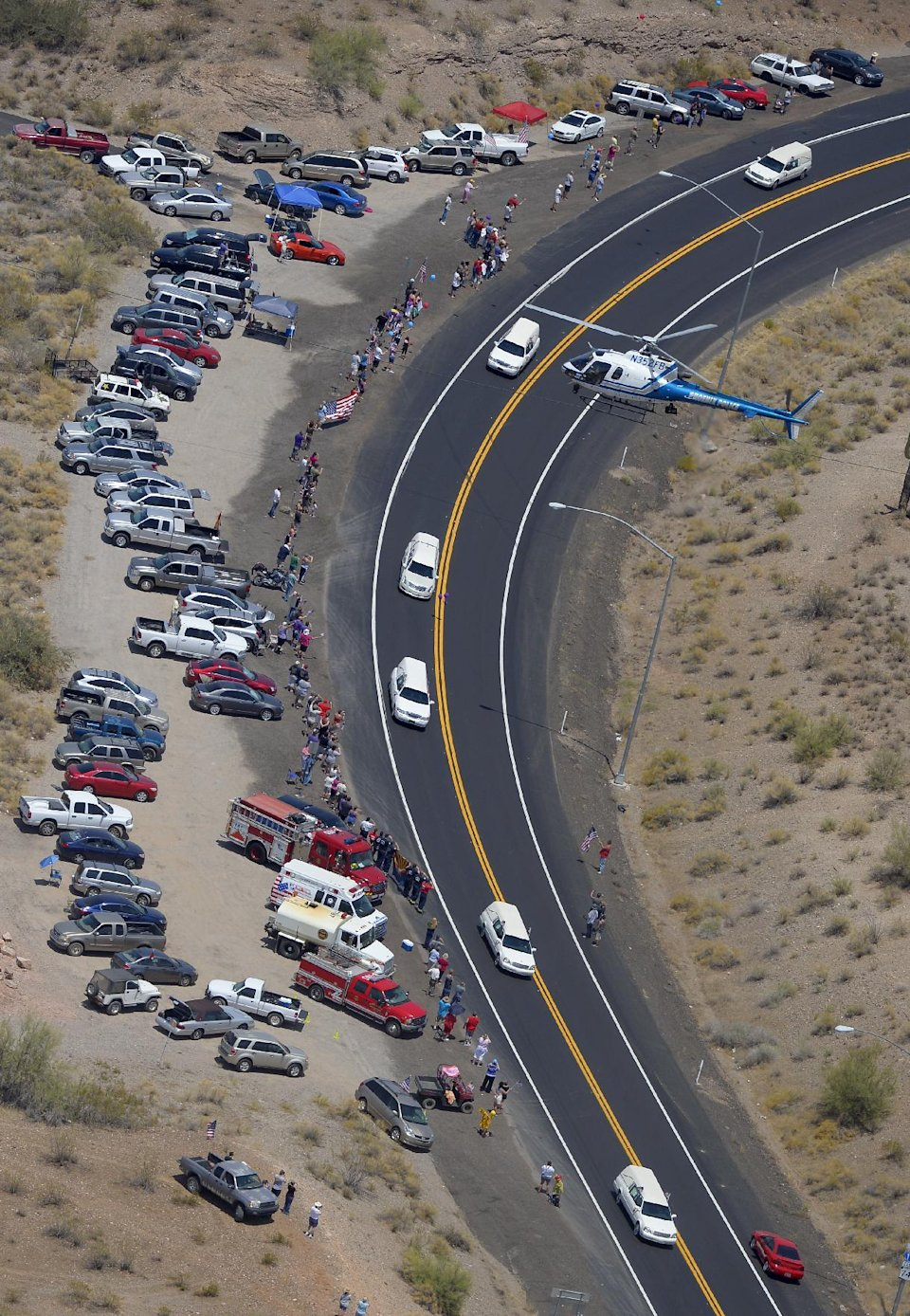 A procession of 19 hearses drives through the desert, Sunday, July 7, 2013, Near Morristown, Ariz, The elite crew of firefighters were overtaken by the out-of-control blaze as they tried to protect themselves from the flames under fire-resistant shields last Sunday. (AP Photo/Mark J. Terrill)