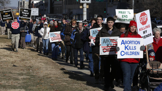 Abortion opponents march to the Kansas Statehouse, and to a rally on the anniversary of Roe v. Wade, in Topeka, Kan., Tuesday, Jan. 22, 2013. Gov. Sam Brownback has signed a series of tough, anti-abortion measures during his first two years in office. Much to the dismay of abortion-rights advocates, Kansas has been part of a wave in which states with Republican governors and GOP-controlled Legislatures enacted new restrictions on abortion providers.  (AP Photo/Orlin Wagner)