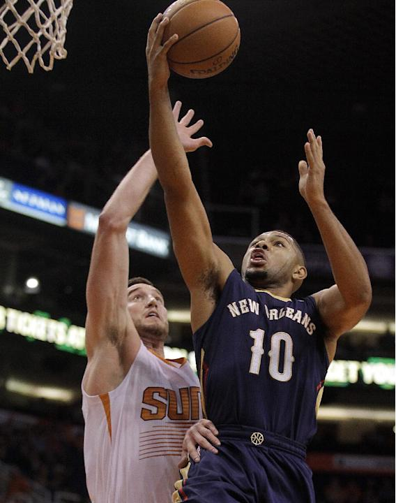 New Orleans Pelicans shooting guard Eric Gordon (10), right, drives past Phoenix Suns center Miles Plumlee (22) in the first quarter during an NBA basketball game on Sunday, Nov. 10, 2013, in Phoenix