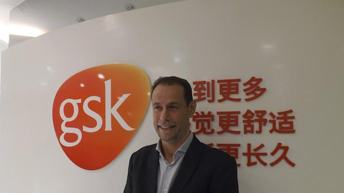 Herve Gisserot, general manager for GSK China, poses for a photograph in front of a company logo during an interview with Reuters at an office in Shanghai