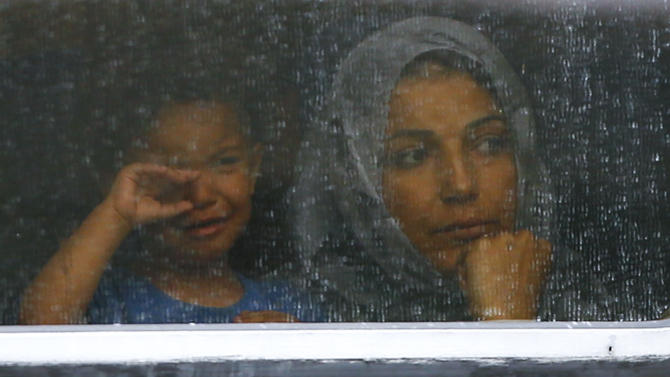 Migrants look out through window of train at railway station in Bicske