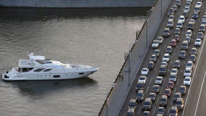 Vehicles are stuck in a traffic jam as a vessel sails along the Moskva river in Moscow