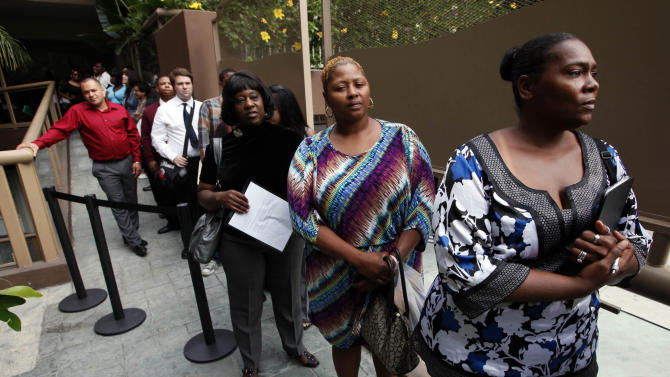 FILE - In this  Friday, Aug. 17 2012, file photo, Sheila Bird, right, waits in line for employment interviews at a job fair at City Target in Los Angeles. U.S. employers advertised slightly fewer jobs in August than July, while they filled the most positions in three months, offering a mixed signal for the job market. (AP Photo/Nick Ut)