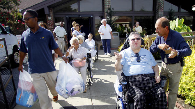 Sentara Nursing Center Currituck resident J.T Campbell, second from right, waits to be evacuated in response to a mandatory evacuation order in Barco, N.C., Friday, Aug. 26, 2011, as Hurricane Irene heads toward the North Carolina coast. Most of the residents will be moved to other Sentara Life Care facilities in Hampton Roads, Virginia. (AP Photo/Jim R. Bounds)