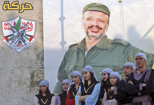 Palestinian performers stand in front of a banner depicting late leader Yasser Arafat during a celebration marking the 47th anniversary of the Fatah movement, in the West Bank town of Jenin, Thursday, Jan. 5, 2012.(AP Photo/Mohammed Ballas)