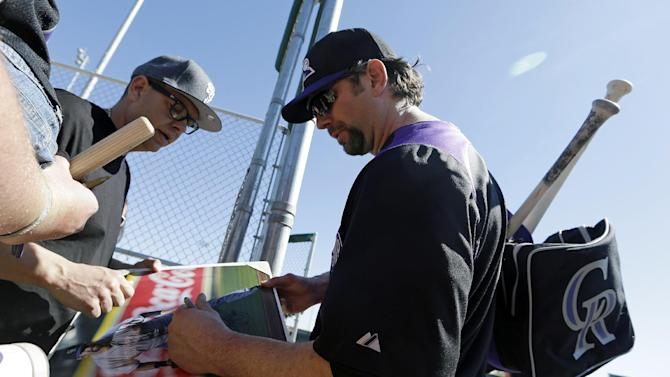 Colorado Rockies' Todd Helton signs autographs for fans during a spring training baseball workout Sunday, Feb. 17, 2013, in Scottsdale, Ariz. (AP Photo/Darron Cummings)