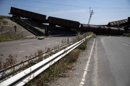 Train wagons are seen on the destroyed railway bridge which collapsed during the fighting between the Ukrainian army and pro-Russian separatists, over a main road leading to the eastern Ukrainian city of Donetsk