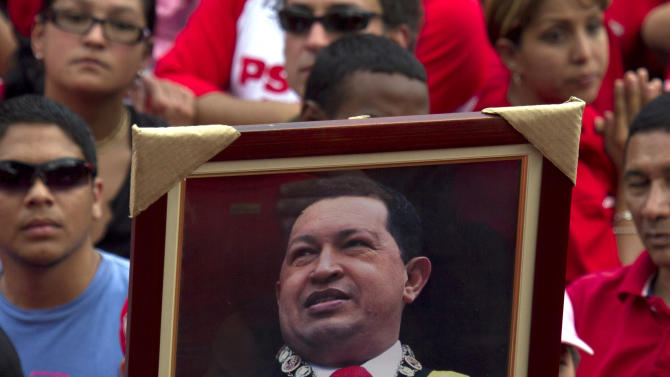 A supporter of Venezuela's President Hugo Chavez holds up a framed image of Chavez as he waits for him to step out on to a balcony to speak at Miraflores presidential palace in Caracas, Venezuela, Saturday March 17, 2012.  Chavez returned to Venezuela Friday nearly three weeks after undergoing cancer surgery in Cuba. (AP Photo/Ariana Cubillos)