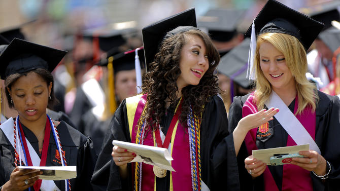 Virginia Tech graduating students, from left: Jasmine Hayes, Kelsey Butler, and Brittany Tatum sing the school Alma Mater at Lane Stadium during the 2013 spring graduation ceremony Friday May 17, 2013 in Blacksburg, Virginia. (AP Photo/The Roanoke Times, Kyle Green)  LOCAL TV OUT; SALEM TIMES REGISTER OUT; FINCASTLE HERALD OUT;  CHRISTIANBURG NEWS MESSENGER OUT; RADFORD NEWS JOURNAL OUT; ROANOKE STAR SENTINEL OUT