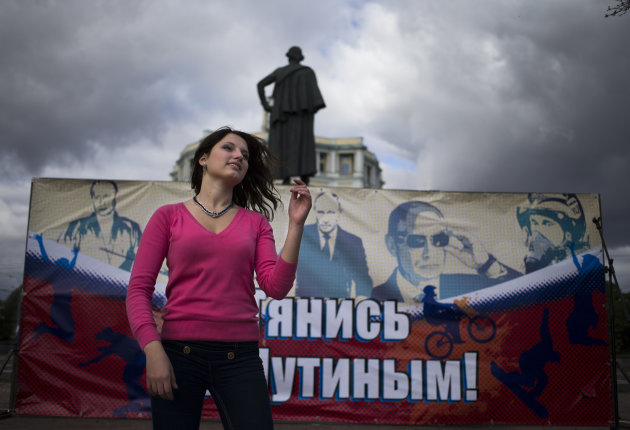 "An activist of the Pro-Kremlin youth movement, Mestnye (locals), dances in front of a poster reading ""Tighten with Putin"" celebrating the 60th birthday of Russian President Vladimir Putin in Moscow, S"